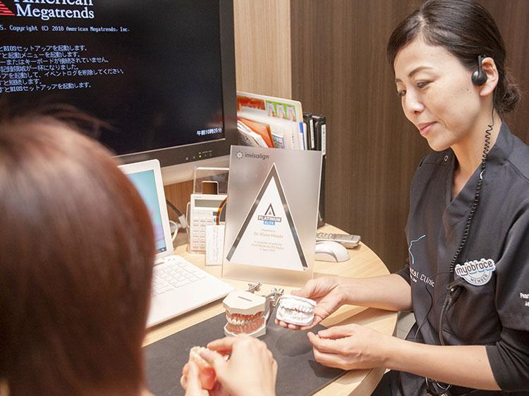 初診矯正カウンセリングで患者様の質問に答える男性歯科医師